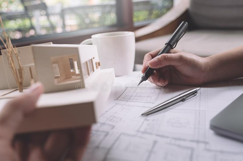 Closeup image of architects drawing shop drawing paper with architecture model. On table stock photo