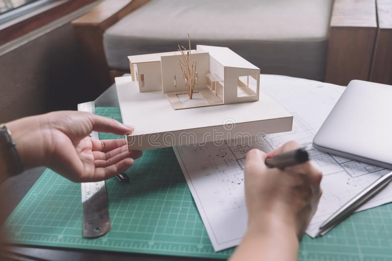 Closeup image of architects drawing shop drawing paper with architecture model. On table royalty free stock photography