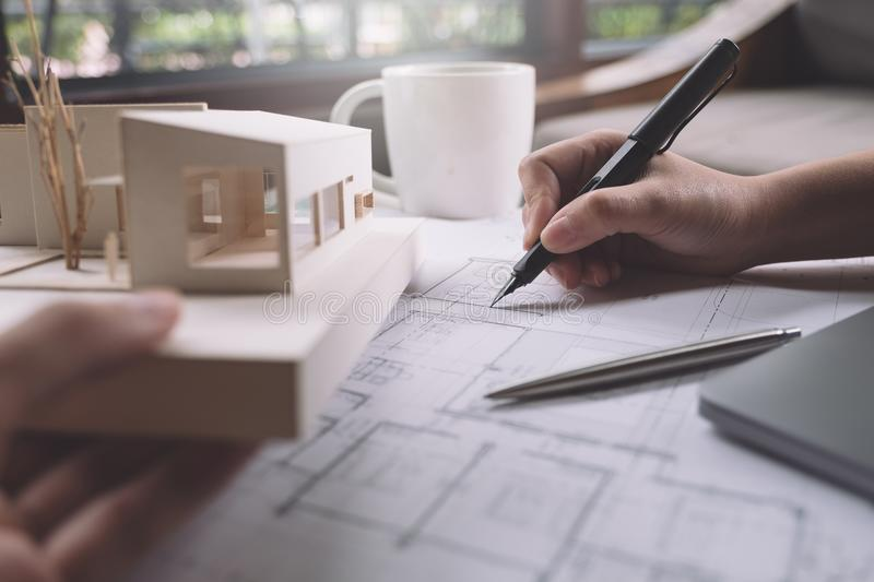 Closeup image of architects drawing shop drawing paper with architecture model royalty free stock image