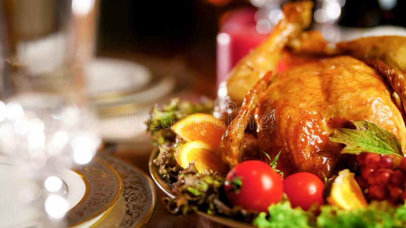 Closeup image of baked chicken with vegetables on served dinner table royalty free stock photography