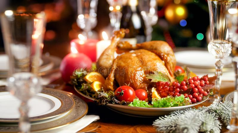 Closeup image of baked turkey on family festive dinner table against burning fireplace. Closeup photo of baked turkey on family festive dinner table against royalty free stock photo