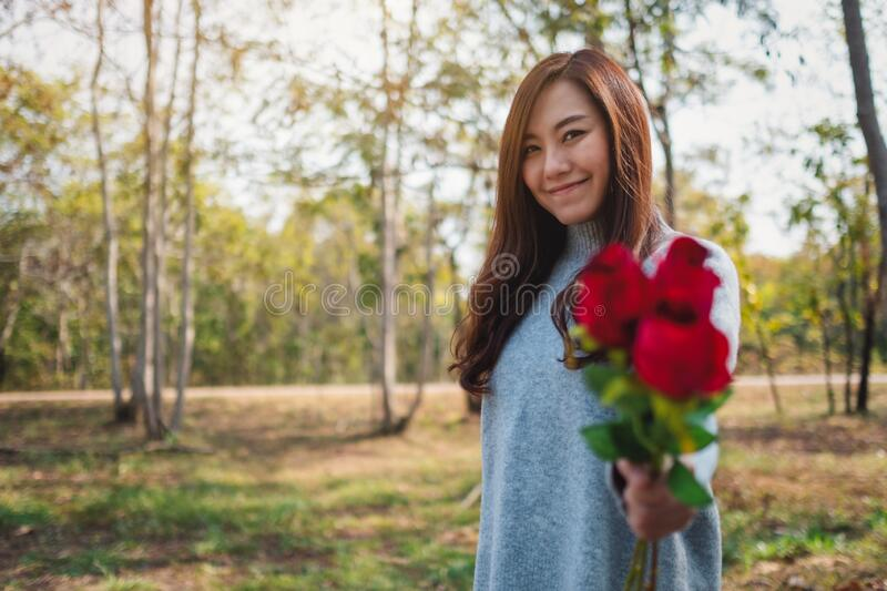 A beautiful asian woman holding and giving red roses flower on Valentine`s day stock photo