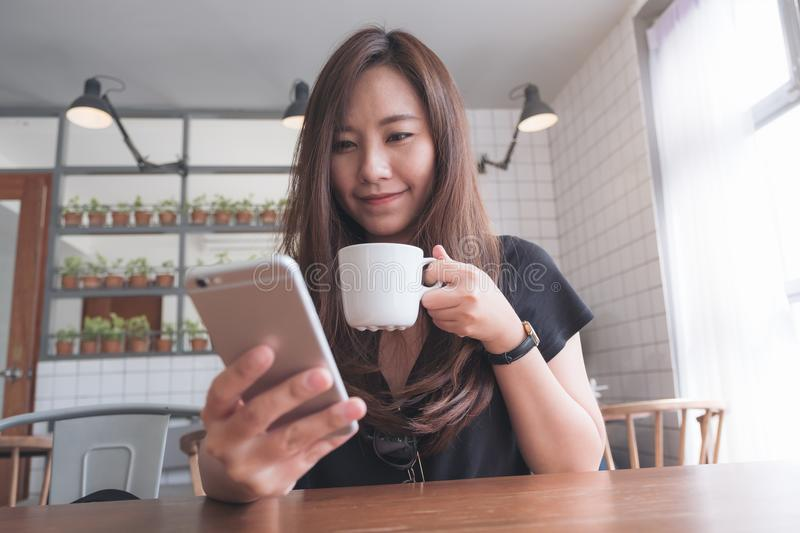 Closeup image of a beautiful Asian woman with smiley face holding and using smart phone while drinking hot coffee on wooden table stock photos