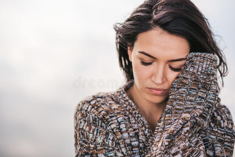 Closeup image of beautiful dreamy female posing against lake with blowing hair. Portrait of romantic female closed eyes enjoying stock images