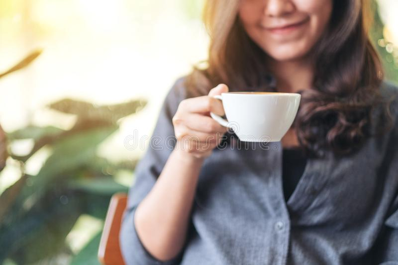 A beautiful woman holding and drinking hot coffee in cafe royalty free stock photography