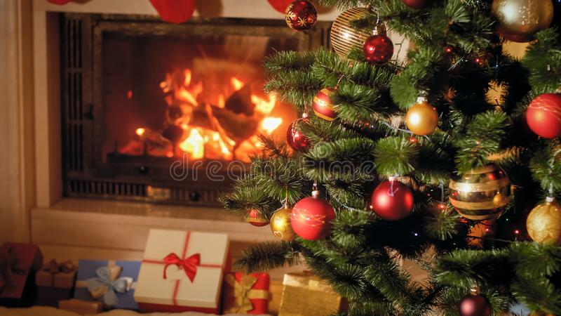 Closeup image of big stack of Christmas gifts and presents next to burning fireplace and decorated Xmas tree. Closeup photo of big stack of Christmas gifts and stock image
