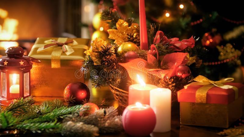 Closeup image of burning candles in traditional wreath against Christmas tree and fireplace royalty free stock images