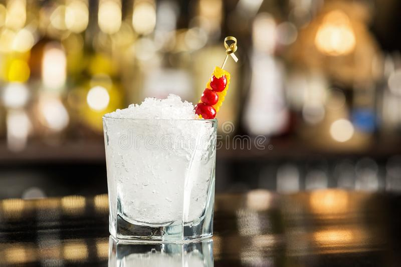 Closeup image of cold glass with soda water and ice at bar royalty free stock images