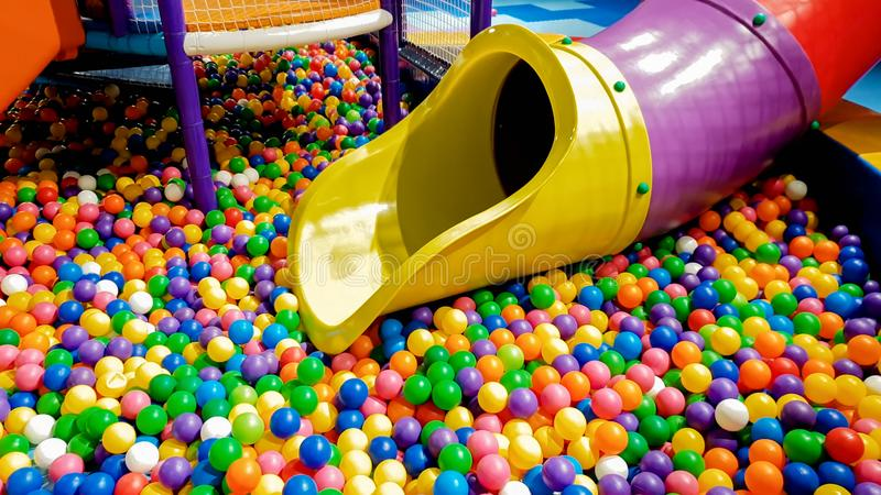 Closeup image of colorful slide on children playground with lots of small plastic ball in the pool. Closeup photo of colorful slide on children playground with royalty free stock images