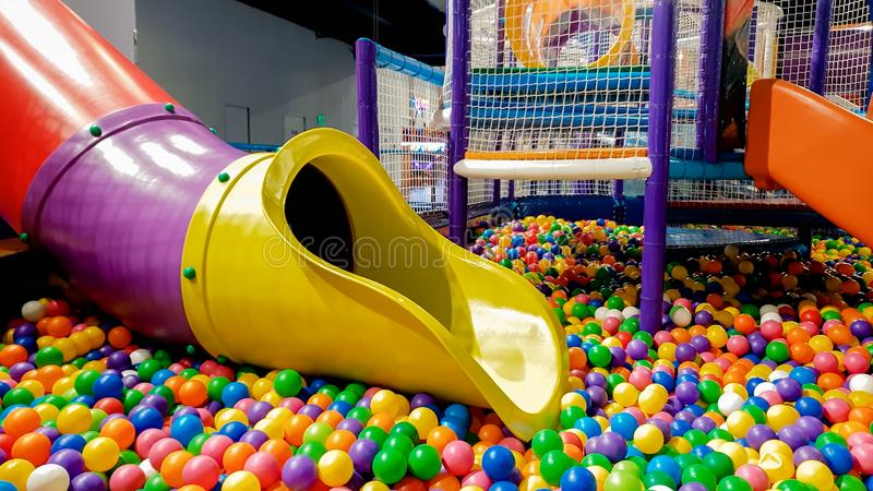 Closeup image of colorful slide on children playground with lots of small plastic ball in the pool. Closeup photo of colorful slide on children playground with stock images