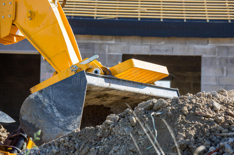 Closeup image of a construction site excavator. An excavator unloading white sand with water at a construction site royalty free stock images