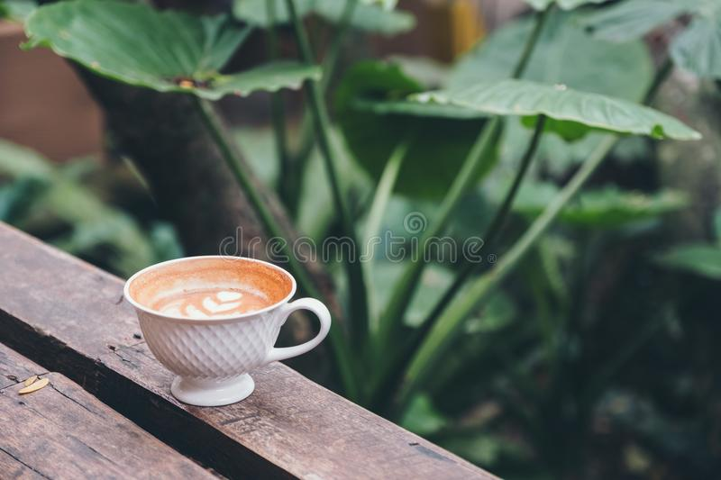 A cup of hot latte coffee with heart latte art on wooden bench in green nature background royalty free stock image