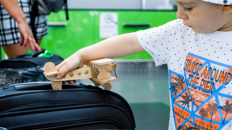Closeup image of cute toddler boy playing with small toy airplane on suitcase. Closeup photo of cute toddler boy playing with small toy airplane on suitcase stock photography