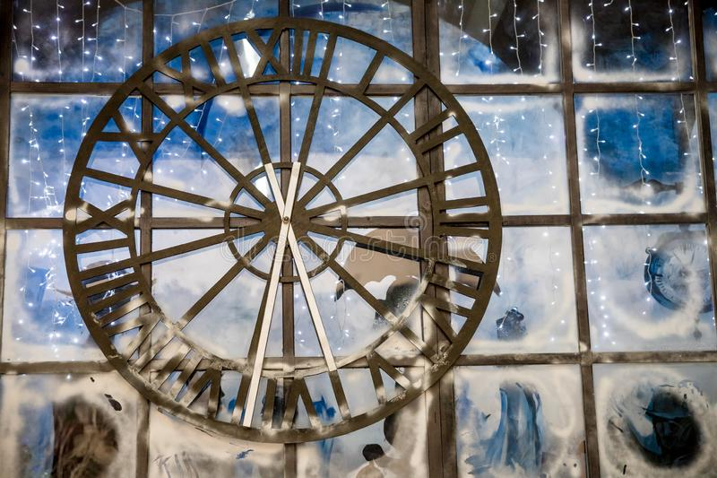 Closeup image of decorated Christmas interior at wall with big clock background.Old rusty big street clock on wall of. Closeup image of decorated Christmas tree stock image