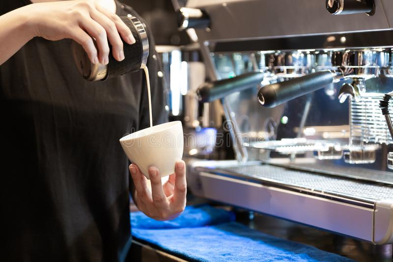Closeup image of female barista pouring milk and preparing fresh cappuccino while standing in front of the coffee machine at. Coffee shop in morning stock images