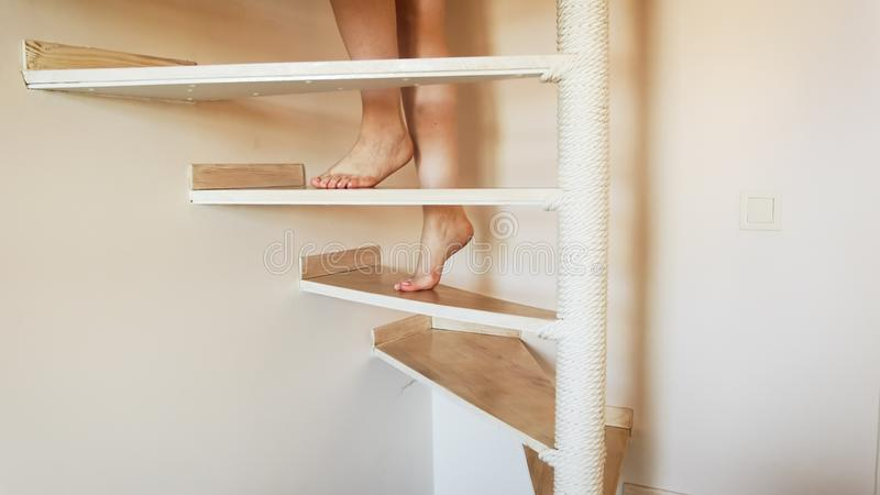 Closeup image of female feet walking up wooden stairs at house royalty free stock images