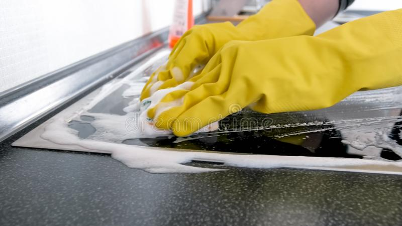 Closeup image of female hands scrubbing electric hob surface with sponge royalty free stock image