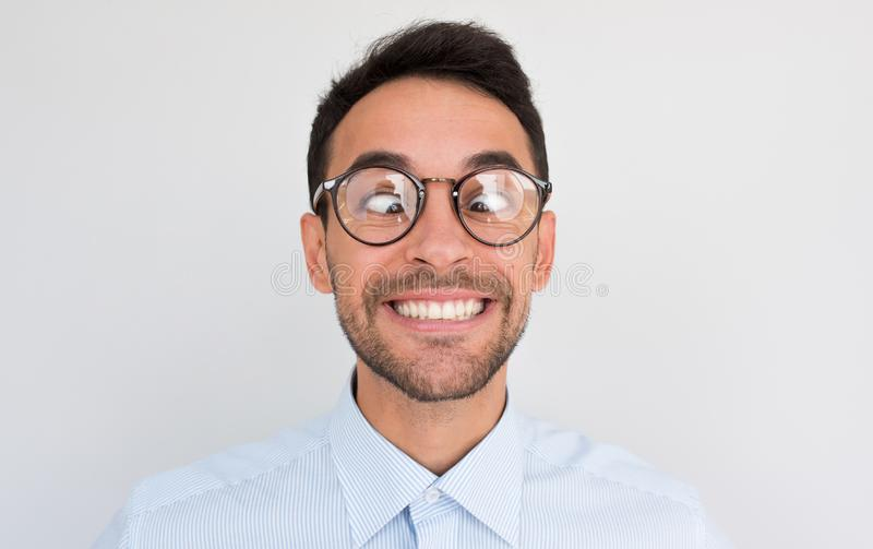 Closeup image of funny comic man crosses eyes, smiling, makes grimace. Clueless male nerd with awkward expression has fun, royalty free stock photography