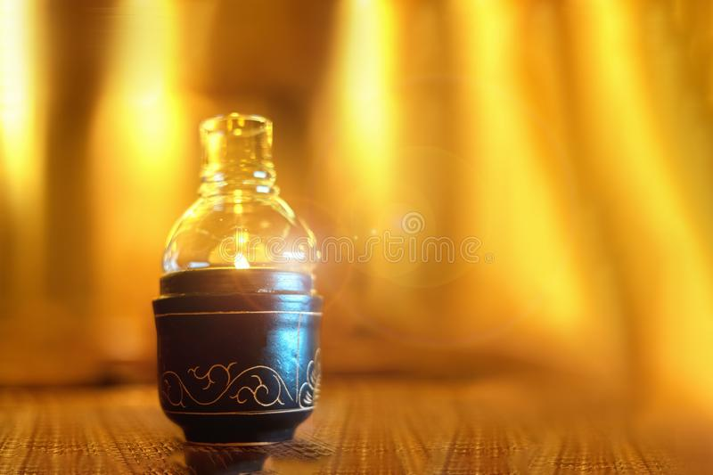 Closeup image of a glass bottle candles holders on wooden table. yellow fire background, ceramics, Thai style, on the stock image