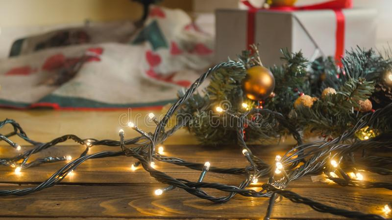 Closeup image of glowing lights garland for Christmas lying on wooden floor stock photography