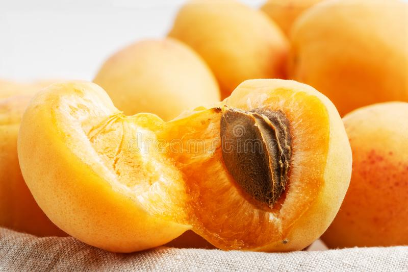 Closeup image of halfed and whole ripe apricot fruits on a cloth napkin. Shallow focus royalty free stock photos