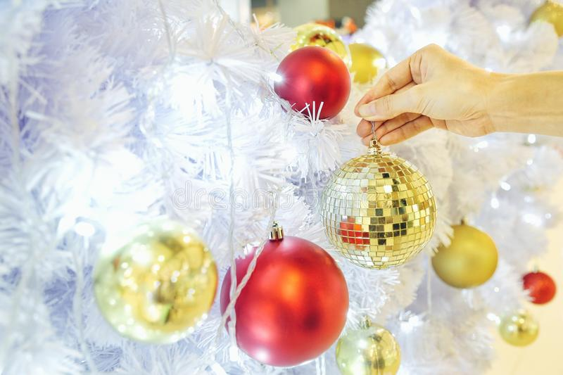Closeup image of a hand decorating white snow Christmas tree with gold sparkling glitter baubles, disco crystal ball style. stock image