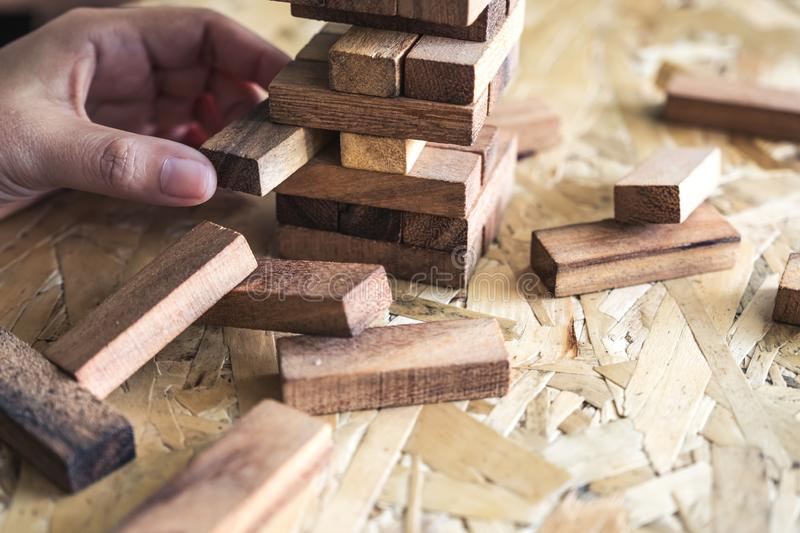 A hand holding and playing Jenga or Tumble tower wooden block game. Closeup image of a hand holding and playing Jenga or Tumble tower wooden block game stock photo