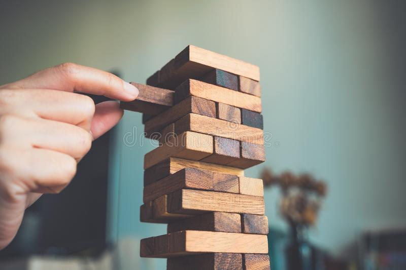 A hand holding and playing Jenga or Tumble tower wooden block game. Closeup image of a hand holding and playing Jenga or Tumble tower wooden block game royalty free stock photography