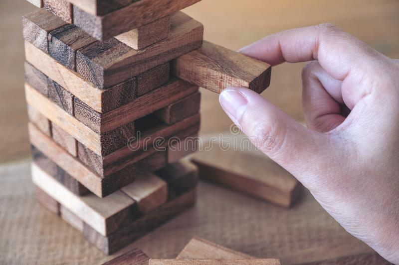 A hand holding and playing Tumble tower wooden block game. Closeup image of a hand holding and playing Tumble tower wooden block game royalty free stock photo