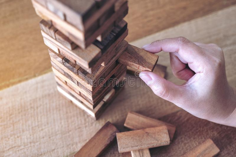 A hand holding and playing Tumble tower wooden block game. Closeup image of a hand holding and playing Tumble tower wooden block game royalty free stock image