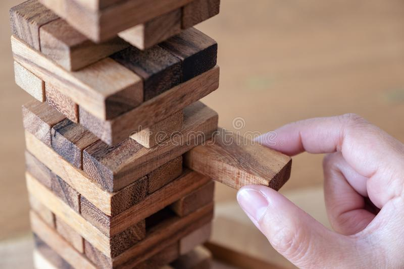 A hand holding and playing Tumble tower wooden block game. Closeup image of a hand holding and playing Tumble tower wooden block game stock image