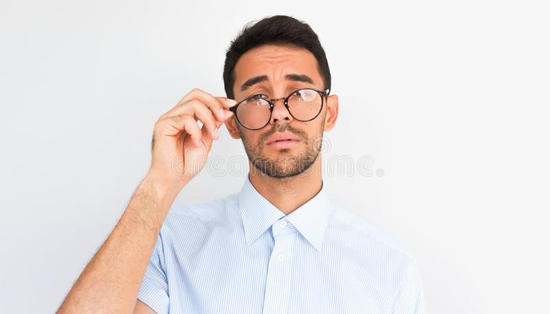 Closeup image of handsome bearded young male looking to the camera, touches rim of round spectacles, wears blue shirt, stands stock photography