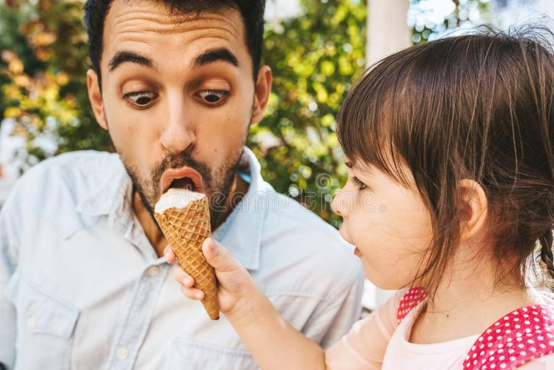 Closeup image of happy cute little girl sitting with handsome dad eating ice-cream outdoors. Fun girl kid and amazed father have royalty free stock photos
