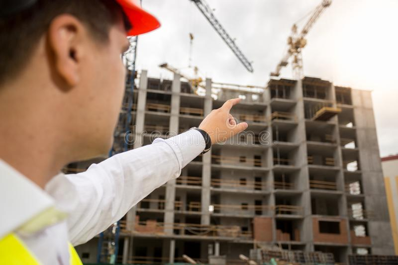 Closeup image of male architect pointing with finger and showing new building under construction royalty free stock image