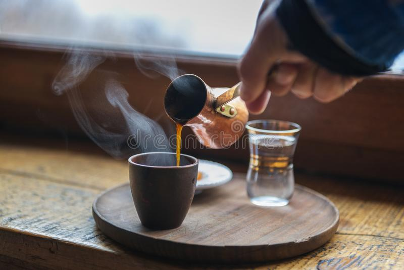 Closeup image of male hand pouring coffee in a vintage cup stock image