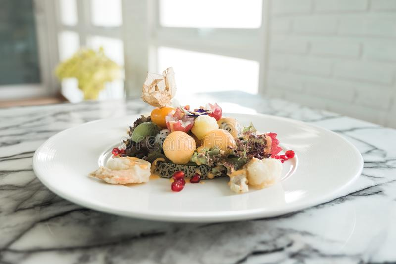 Closeup image of mixed fruits salad with fried shrimps on white plate royalty free stock photography