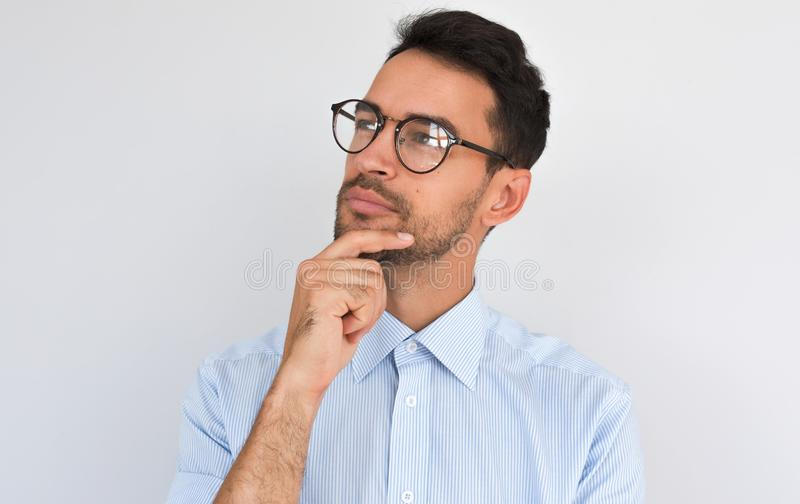 Closeup image of pleased pensive male keeps hand under chin, looking aside, on white studio background. Successful unshaven man royalty free stock images
