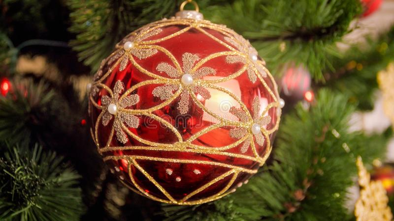 Closeup image of shiny red bauble with golden glitter on Christmas tree branch royalty free stock photo