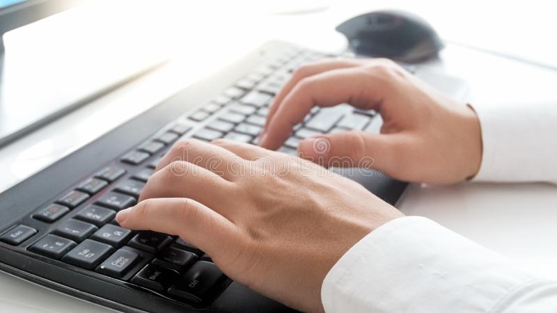 Closeup photo of slim female hands typing text on computer keyboard royalty free stock image