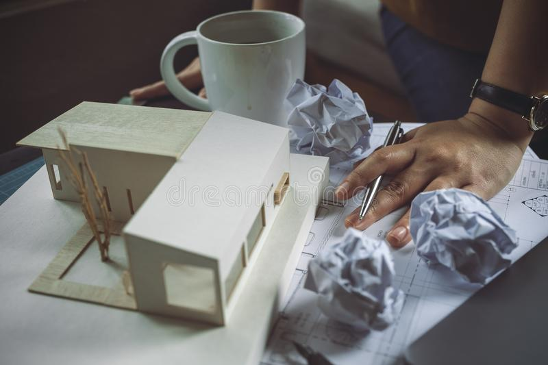 Closeup image of a stressed architects thinking and drawing shop drawing paper with architecture model and laptop on table. While fail royalty free stock photo