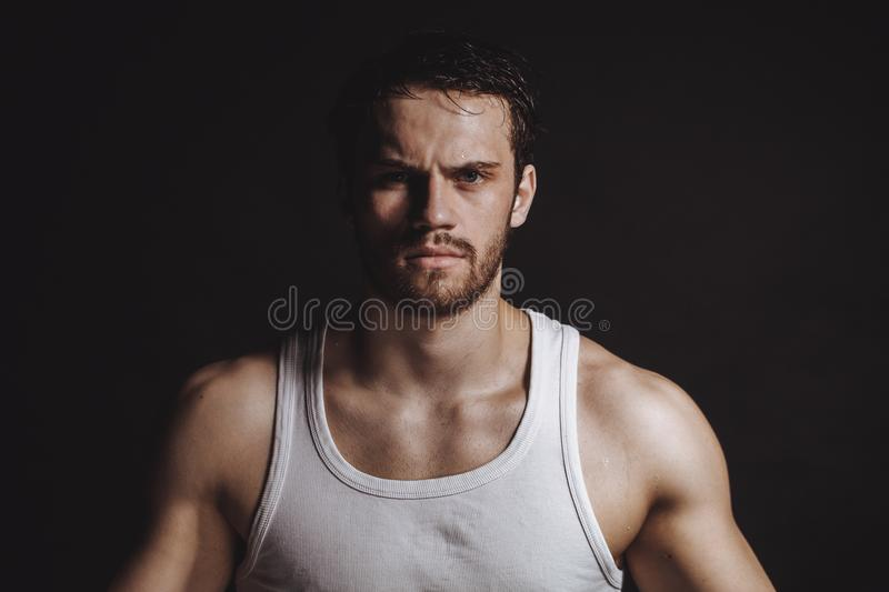 Closeup image of strong sweaty sportsman in white shirt after physical trainings. Hard exercises royalty free stock photo