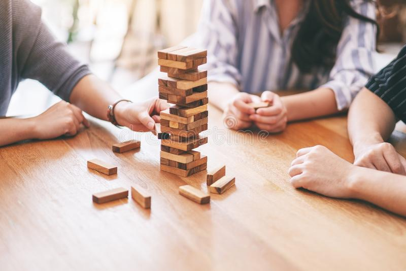Three friends sitting and playing Tumble tower wooden block game together. Closeup image of three friends sitting and playing Tumble tower wooden block game stock photo