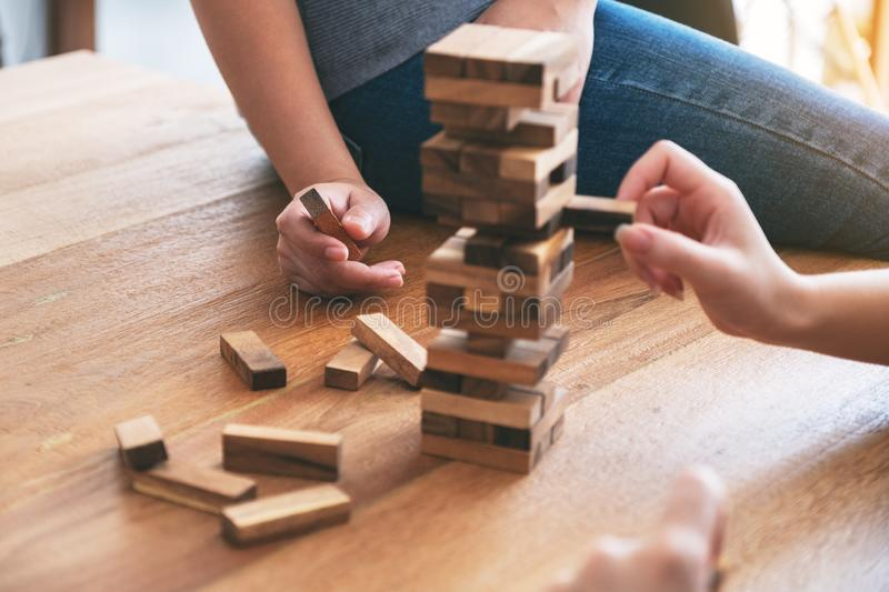 Three friends sitting and playing Tumble tower wooden block game together. Closeup image of three friends sitting and playing Tumble tower wooden block game royalty free stock image