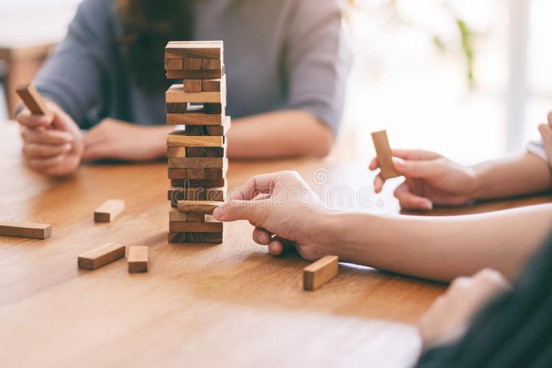 Three friends sitting and playing Tumble tower wooden block game together. Closeup image of three friends sitting and playing Tumble tower wooden block game royalty free stock photos