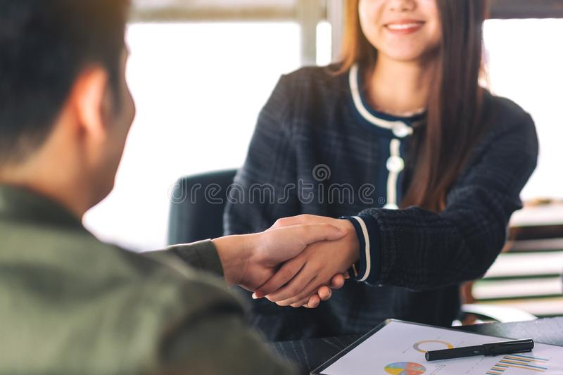 Two businesspeople shaking hands in a meeting. Closeup image of two businesspeople shaking hands in a meeting stock photos