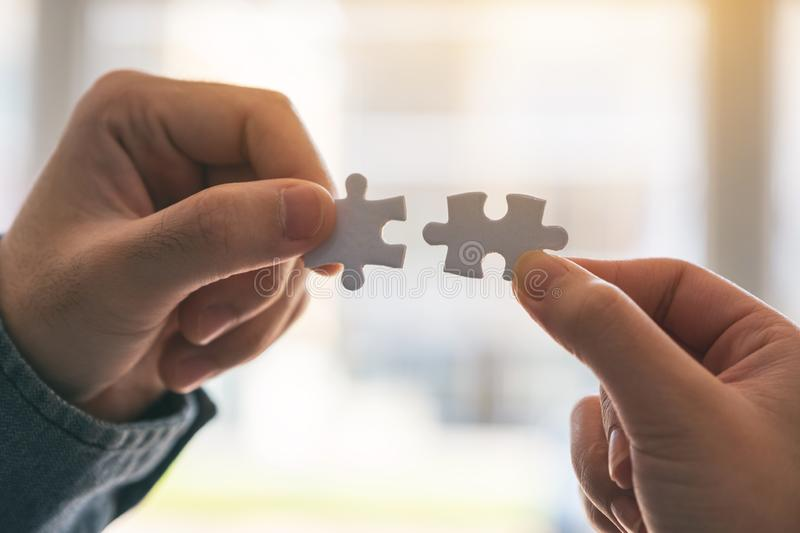 Two hands holding and putting a piece of white jigsaw puzzle together royalty free stock images
