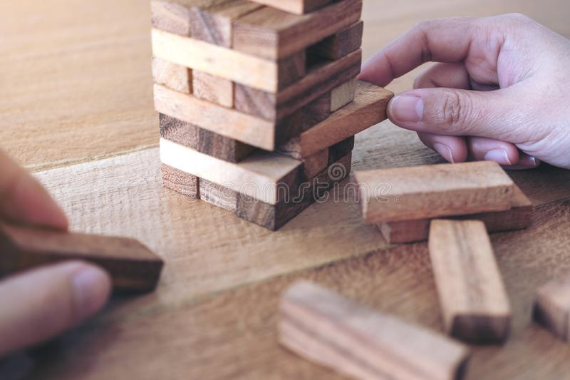 Two people`s hand holding and playing Tumble tower wooden block game. Closeup image of two people`s hand holding and playing Tumble tower wooden block game stock image