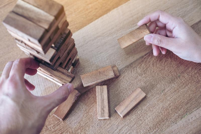 Two people`s hand holding and playing Tumble tower wooden block game. Closeup image of two people`s hand holding and playing Tumble tower wooden block game stock images
