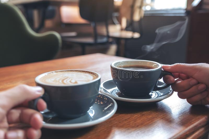 Two people`s hands holding coffee and hot chocolate cups on wooden table in cafe. Closeup image of two people`s hands holding coffee and hot chocolate cups on royalty free stock photos