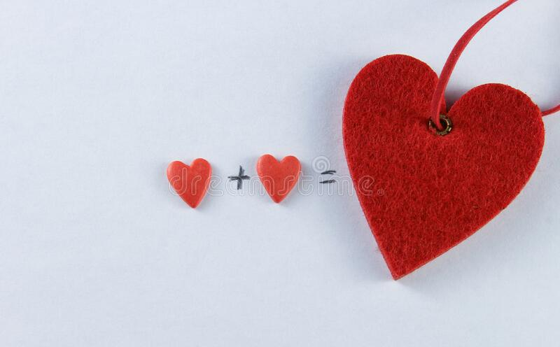 Closeup image of two red hearts with a plus and equal sign on a white background, valentines day, valentines day.  stock photography